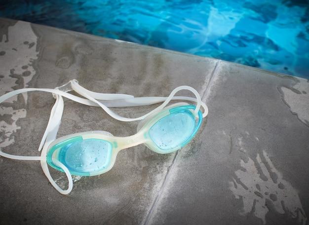 Óculos de natação modernos azuis colocados ao lado da piscina.