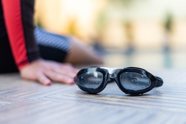 Óculos de natação pretos de conceito de esportes e recreação colocados em uma piscina com um menino vestindo um maiô.