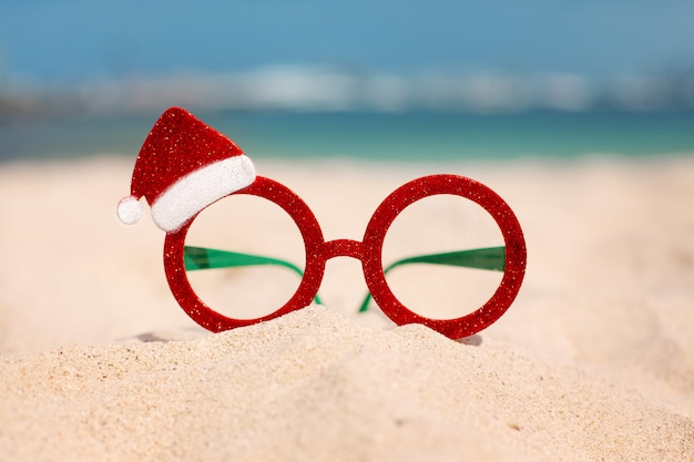 Óculos de natal vermelho e chapéu de papai noel na praia
