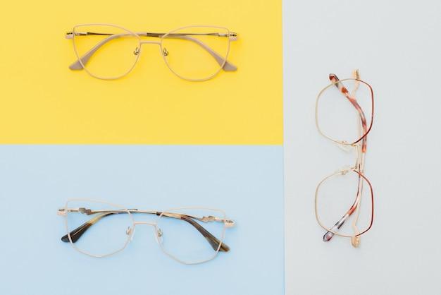 Óculos de olhos modernos e elegantes para correção de visão em um fundo colorido, fundo geométrico de papel de cores pastel