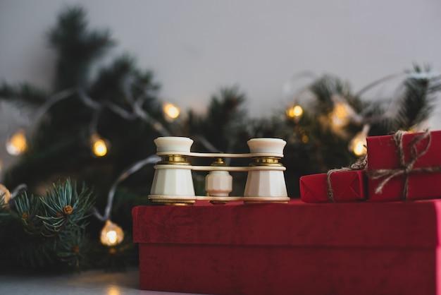 Óculos de ópera, ramo de abeto, caixas de presente vermelhas e guirlanda de natal