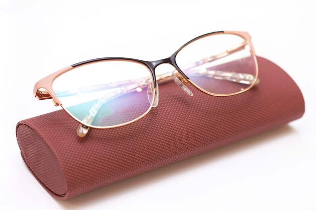 Óculos de ouro das mulheres na moda moderna para visão e um estojo de couro sobre um fundo claro.