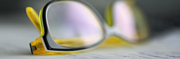 Óculos de plástico amarelos, deitado na mesa de trabalho pronta para ser usado close-up