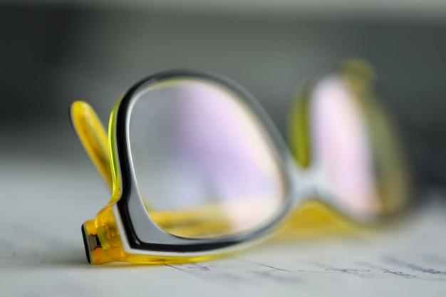 Óculos de plástico amarelos, deitado na mesa de trabalho