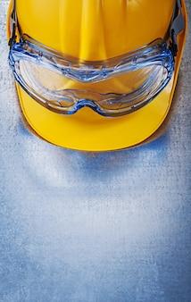 Óculos de plástico, capacete de construção na mesa metálica, conceito de construção