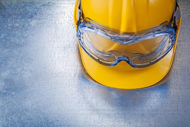 Óculos de plástico, capacete de construção na mesa metálica