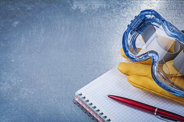 Óculos de plástico luvas de couro caderno caneta na superfície metálica