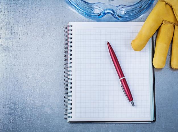 Óculos de plástico luvas de segurança caderno caneta na mesa metálica