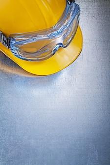 Óculos de proteção capacete de plástico na mesa metálica
