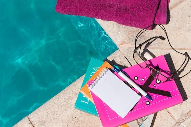 Óculos de proteção com livros e bloco de notas perto de toalha e piscina