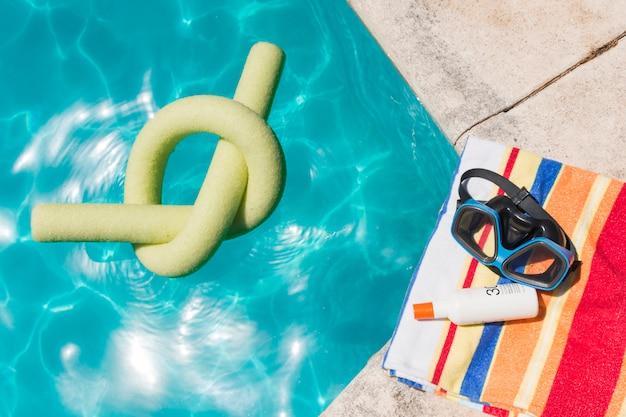 Óculos de proteção com loção na toalha perto da piscina