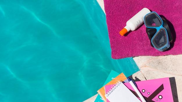 Óculos de proteção com loção na toalha perto de livros e piscina