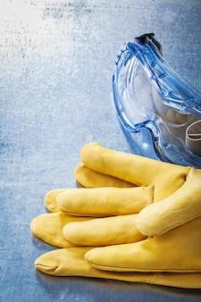 Óculos de proteção de plástico luvas de segurança na mesa metálica riscada