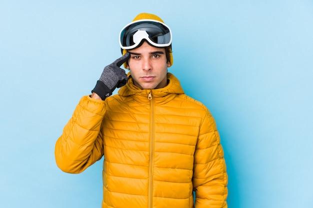 Óculos de proteção do snowboard homem jovem esquiador isolado mostrando um gesto de decepção com o dedo indicador.