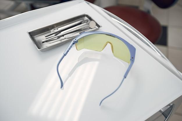 Óculos de proteção no consultório do dentista. as ferramentas ficam em uma bandeja. preparando o dentista antes da admissão