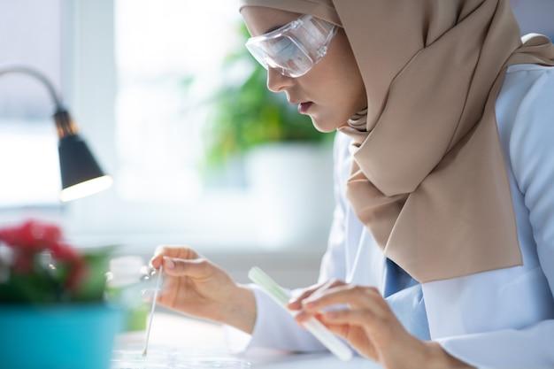 Óculos de proteção. química feminina usando óculos de proteção e hijab fazendo algumas experiências