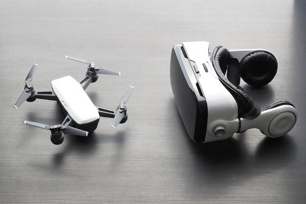 Óculos de realidade virtual e pequeno avião na mesa de madeira escura.
