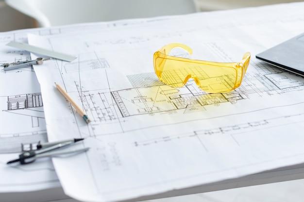 Óculos de segurança amarelo closeup no projeto arquitetônico