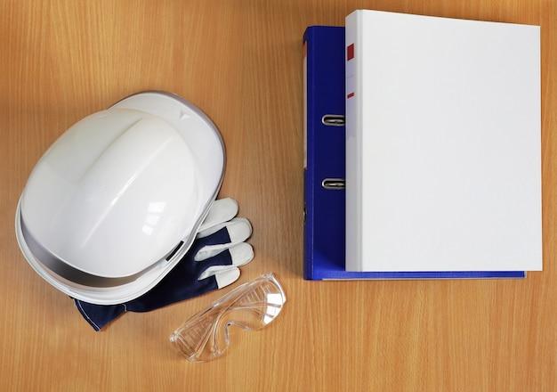 Óculos de segurança de capacete de construção branco na mesa com pastas na horizontal