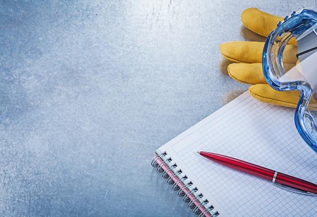 Óculos de segurança luvas de couro caderno caneta na mesa metálica