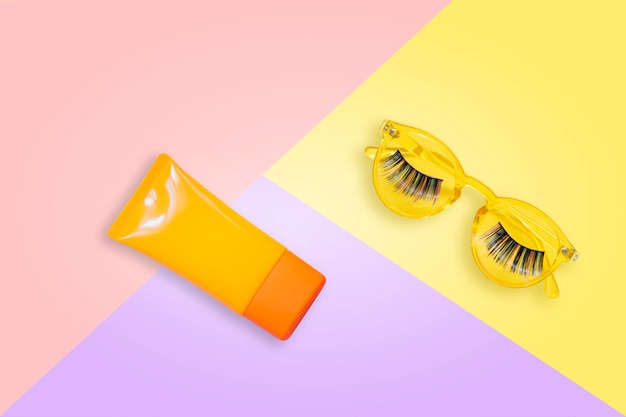 Óculos de sol amarelos com cílios postiços e laranja creme protetor solar spf em fundo rosa.