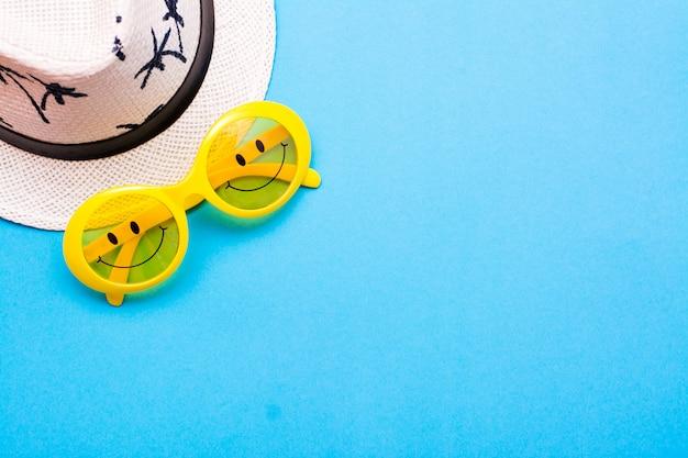 Óculos de sol amarelos de plástico com olhos pintados e um sorriso nos óculos e um chapéu em um fundo azul