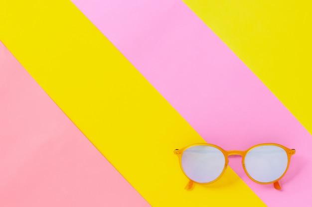Óculos de sol amarelos isolados em fundo colorido.