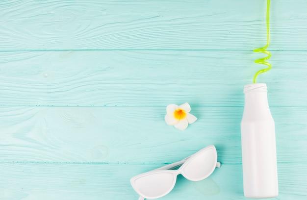 Óculos de sol brancos e garrafa com palha