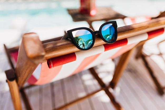 Óculos de sol brilhantes deitado na poltrona.