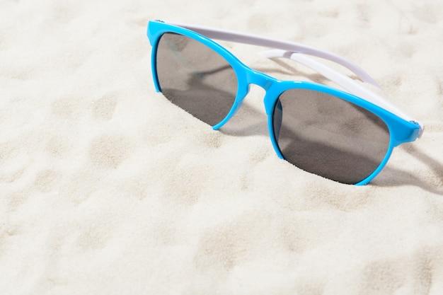 Óculos de sol brilhantes na areia