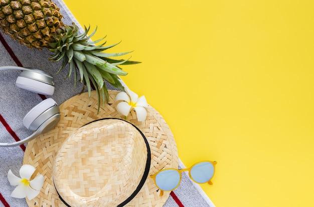 Óculos de sol, chapéu de praia, fone de ouvido sem fio, flores de abacaxi e frangipani em fundo amarelo
