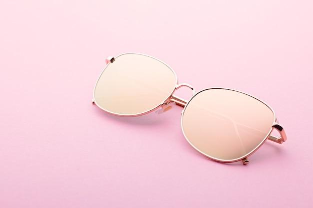 Óculos de sol clássico aviador de lentes planas espelhadas com close up de armação de metal dourado sobre fundo rosa