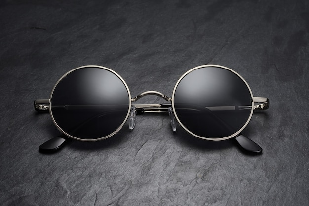 Óculos de sol clássicos redondos de metal cinza com fundo de ardósia preta