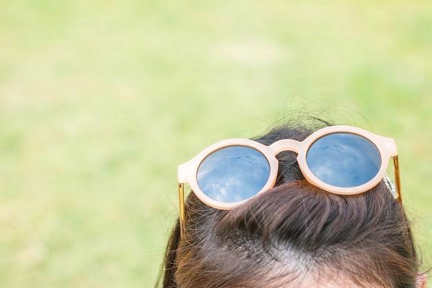 Óculos de sol closeup na cabeça de mulher com fundo de textura de grama verde turva
