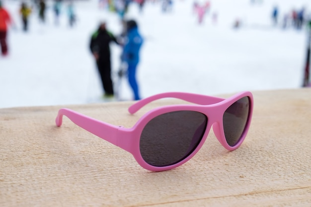 Óculos de sol com armação rosa na encosta de madeira em um bar ou café apres ski, com uma pista de esqui no fundo. conceito de esportes de inverno, lazer, recreação, relaxamento no resort. horizontal.