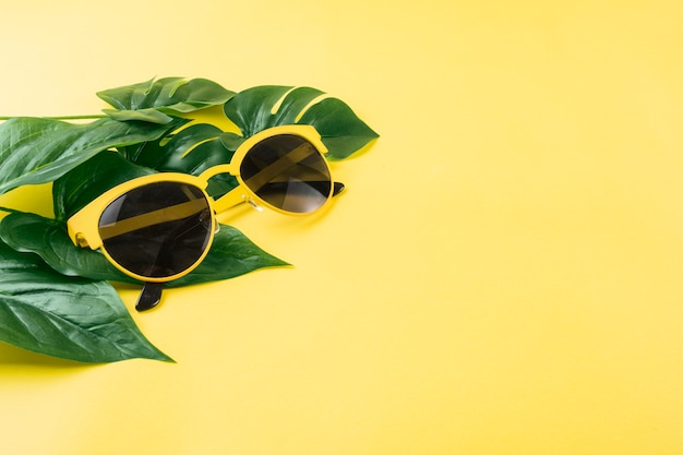 Óculos de sol com folhas verdes artificiais sobre fundo amarelo
