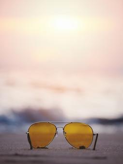 Óculos de sol com lente amarela na areia na praia do sol.