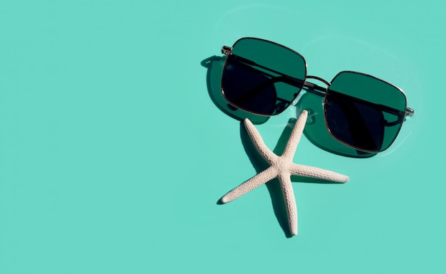 Óculos de sol com peixe estrela sobre fundo azul. aproveite o conceito de férias.