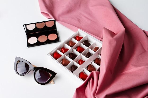 Óculos de sol cosméticos decorativos e chocolate sobre a superfície branca