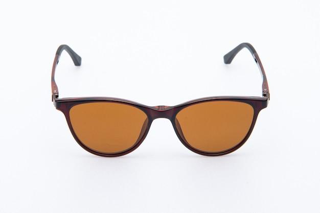 Óculos de sol da moda, armações marrons e lentes laranja em fundo branco