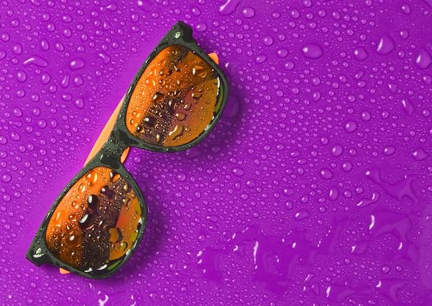 Óculos de sol da moda em gotas de água sobre um fundo violeta brilhante. vista do topo.