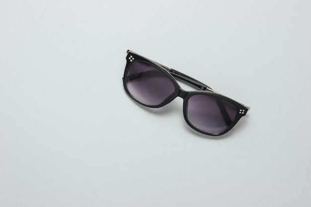 Óculos de sol da moda feminina em uma mesa cinza. vista do topo.
