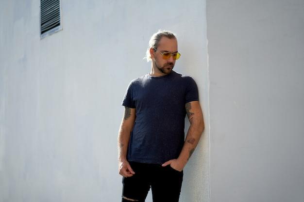 Óculos de sol de camisa azul jovem barbeado jovem bonito amarelo fica perto de paredes brancas dia de verão. com espaço livre para seu texto