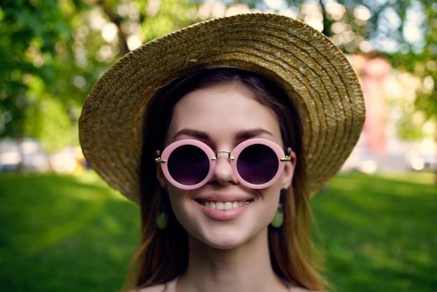 Óculos de sol de mulher e um chapéu na grama verde do parque