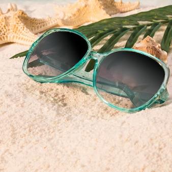 Óculos de sol deitado na praia de areia