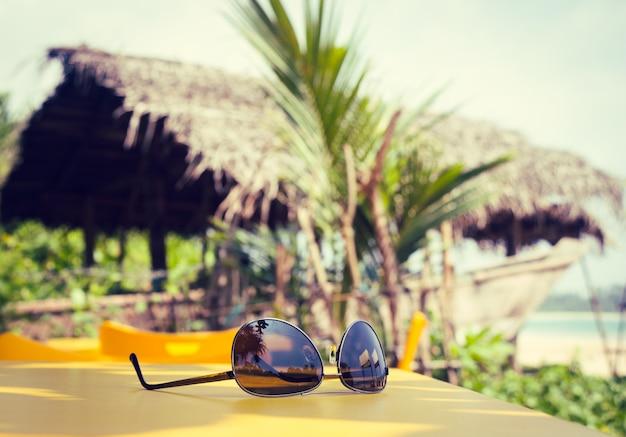 Óculos de sol deitado sobre uma mesa amarela em um café de praia tropical