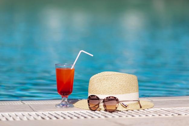 Óculos de sol do chapéu e bebida perto da piscina