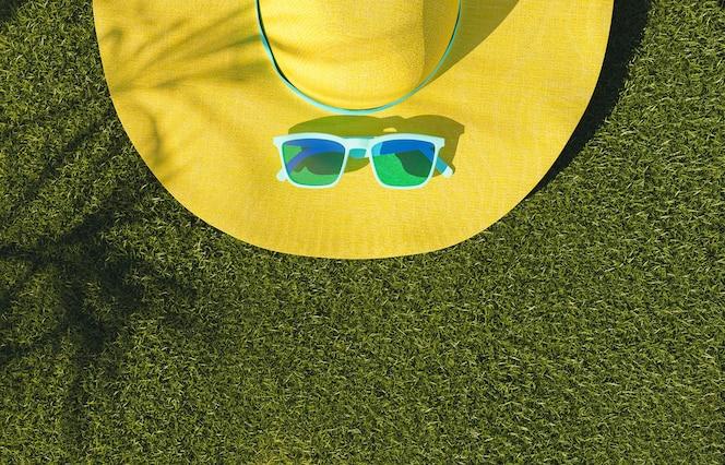 Óculos de sol e chapéu amarelo no conceito de verão gramado