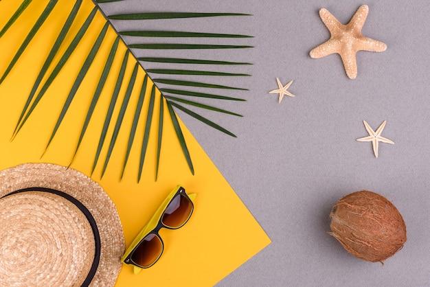 Óculos de sol e chapéu com conchas e estrelas do mar em uma superfície colorida