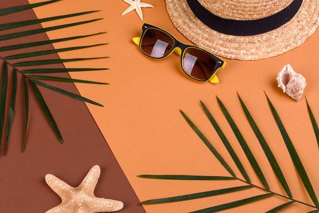 Óculos de sol e chapéu com conchas e estrelas do mar em uma superfície colorida Foto Premium